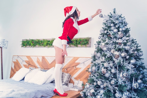 Sexy women in the clothes of santa claus holding christmas ball for christmas tree. sexy girl decorates the flat to celebrate the new year and christmas in bedroom with modern design.