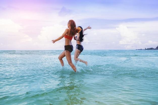 セクシーな女性の自由な休暇は海に走っているビーチの友達でリラックスして休暇を楽しむ