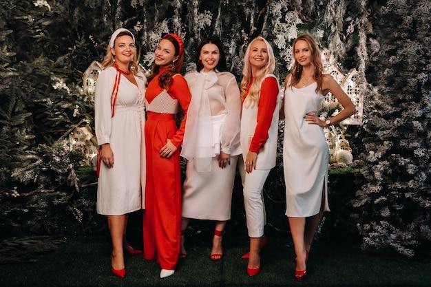 お祝いの白と赤の服を着たセクシーな女性がクリスマスの背景に立っています