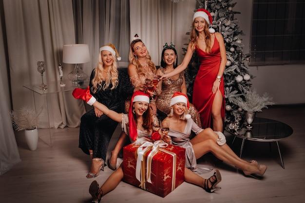 샴페인과 큰 선물의 안경 산타 모자에 섹시 한 여자. 새해 휴일입니다. 크리스마스 이브. 홈 인테리어의 배경. 새해 복 많이 받으세요