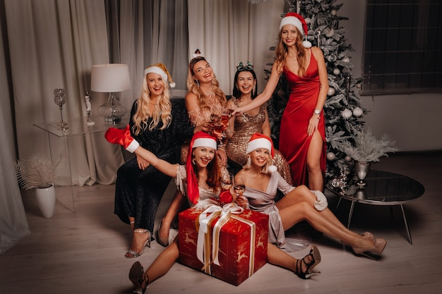 シャンパングラスと大きな贈り物とサンタの帽子のセクシーな女性。元日。クリスマス・イブ。家のインテリアの背景に。あけましておめでとう