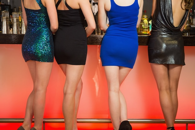 Сексуальные ноги женщины стоят в баре