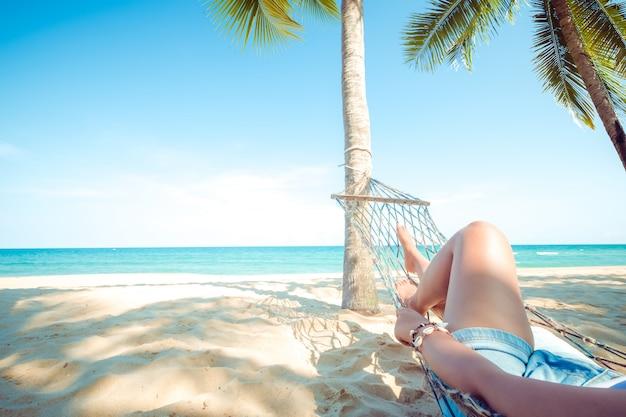 섹시 한 여자 휴식과 모래 열 대 해변에서 해먹에 일광욕.