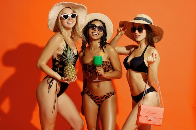 Sexy women in swimsuits, hats and sunglasses on orange