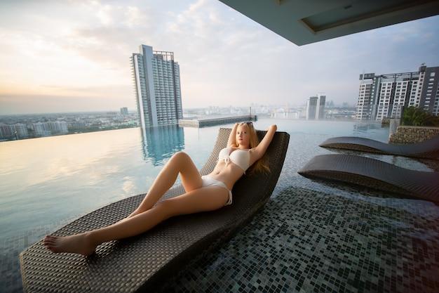 プールサイドでベッドに横たわっている白いビキニのセクシーな女性。