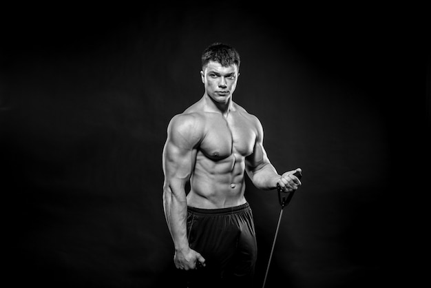 Sexy young athlete posing on black