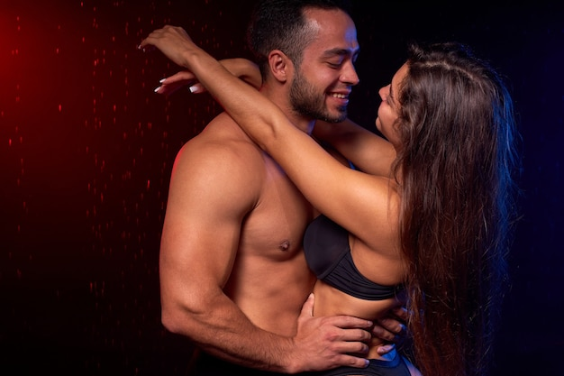 Sexy young beautiful couple posing hugging under heavy rain on black background