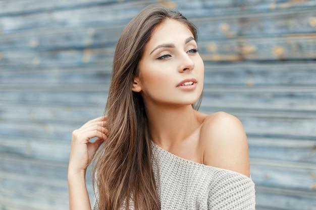 青い木製の壁の近くのヴィンテージの灰色のセーターのセクシーな若い美しい女性