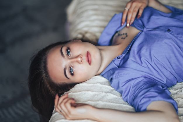 Sexy young beautiful woman with blue big eyes lond hair lying on bed at home in blue shirt