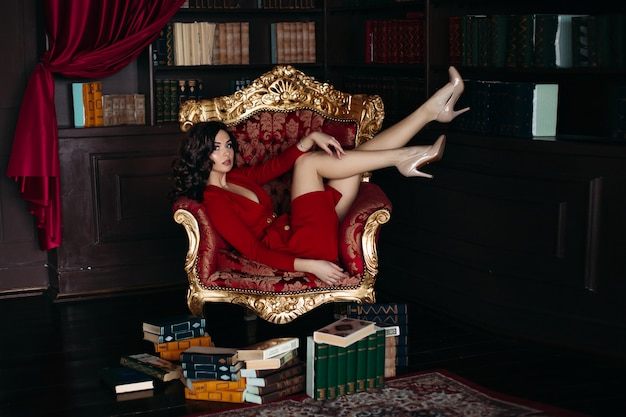 Sexy young brunette lying on big armchair in library.