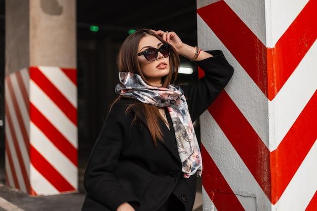 シルクの春のスカーフとトレンディな黒のコートでスタイリッシュなサングラスをかけたセクシーな若いブルネットの女性は、都市の駐車場の縞模様の列の近くで休んでいます。エレガントな美しい女の子のファッションモデル。現代のビジネスレディ。