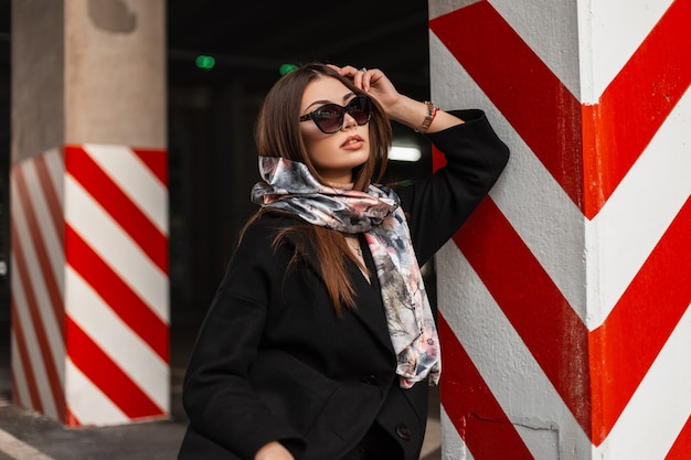 Sexy young brunette woman in stylish sunglasses in trendy black coat with silk spring scarf is rest near striped column in a city parking. elegant beautiful girl fashion model. modern business lady.