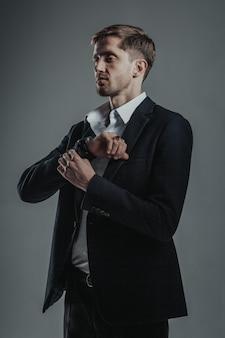 セクシーな青年実業家はスタイリッシュな服を着て、彼のフリルにボタンをかけ、よそ見をしました。
