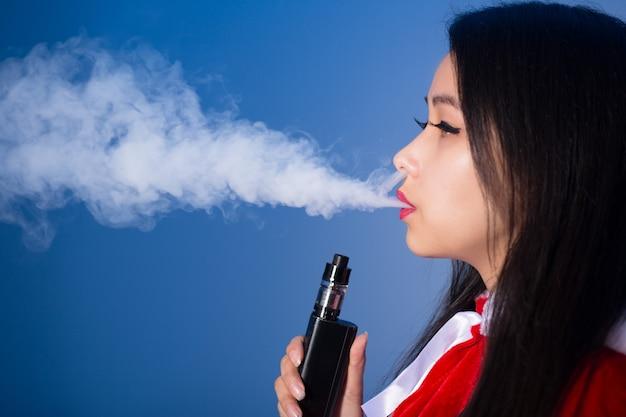 Сексуальная молодая китаянка в костюме санта-клауса курит электронную сигарету и выдыхает пар на синем фоне