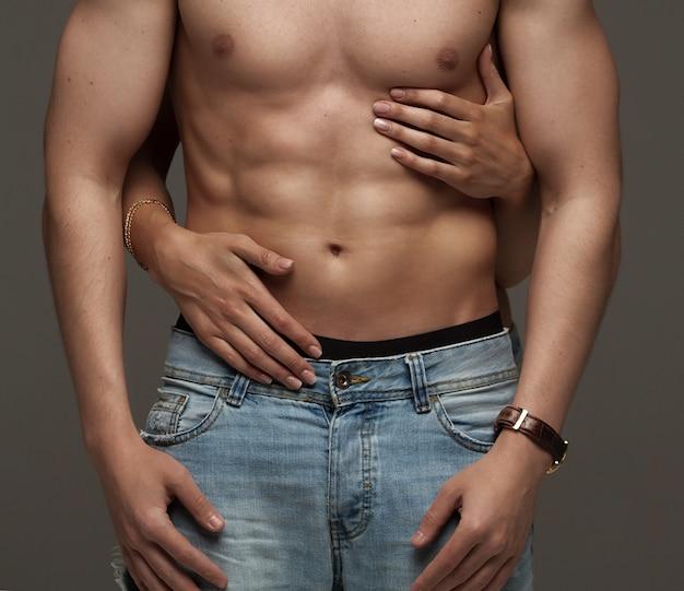 Сексуальная молодая пара. красивая сексуальная влюбленная пара на сером фоне оделась в синих джинсах.