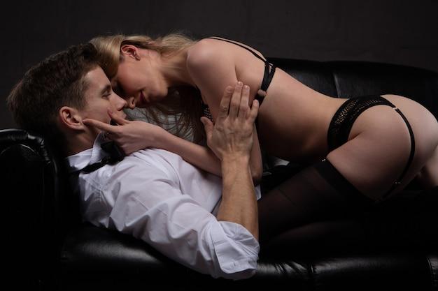 愛のセクシーな若いカップルは、黒いソファに横たわって情熱的にキスします。