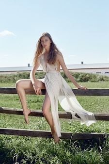 필드에 나무 울타리에 앉아 포즈 빛 흰색 드레스에 섹시 한 젊은 패션 여자. 시골 풍경을 배경으로 완벽한 모습을 한 소녀