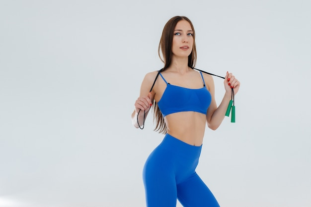 Sexy young girl jumping rope in a blue tracksuit on a white space. fitness, healthy lifestyle.