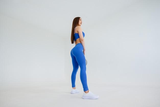 섹시 한 젊은 여자는 파란색 운동복에 무게와 운동을 수행합니다. 피트니스, 건강한 라이프 스타일.