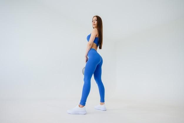 섹시 한 젊은 여자는 흰색 표면에 파란색 운동복에 무게와 운동을 수행