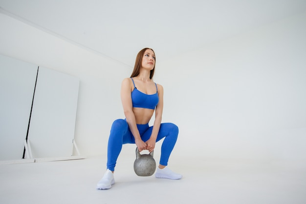Sexy young girl performs exercises with a weight in a blue tracksuit on a white wall. fitness, healthy lifestyle.