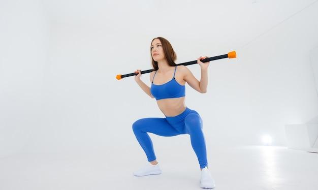 セクシーな若い女の子は白い表面でスポーツの練習を行います
