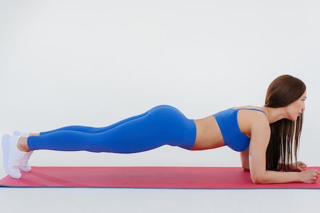 섹시 한 젊은 여자는 흰 벽에 스포츠 연습을 수행합니다. 피트니스, 건강한 라이프 스타일.