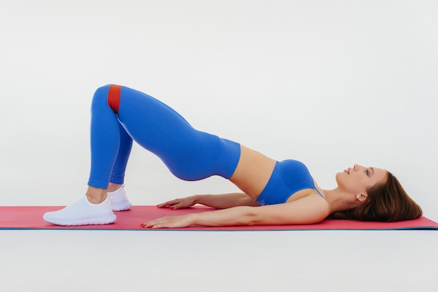 Sexy young girl performs sports exercises on a white background. fitness, healthy lifestyle.