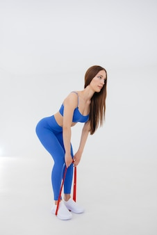 Sexy young girl performs sports exercises on a white space. fitness, healthy lifestyle.