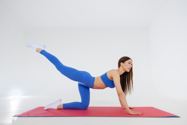 Sexy young girl performs sports exercises on a white wall. fitness, healthy lifestyle.