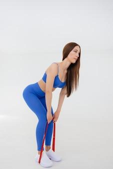 Сексуальная молодая девушка выполняет спортивные упражнения