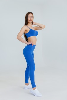 Sexy young girl posing in a blue tracksuit on a white space. fitness, healthy lifestyle.