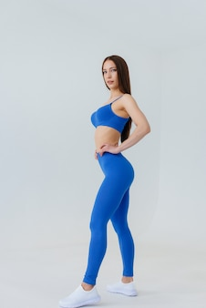 Sexy young girl posing in a blue tracksuit on a white wall. fitness, healthy lifestyle.