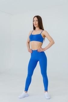 흰 벽에 파란색 운동복에 포즈 섹시 한 젊은 여자. 피트니스, 건강한 라이프 스타일.