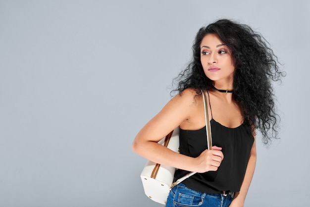 Sexy young girl with black curly hair carrying white backpack with a golden zipper. she wears black light top and blue jeans.