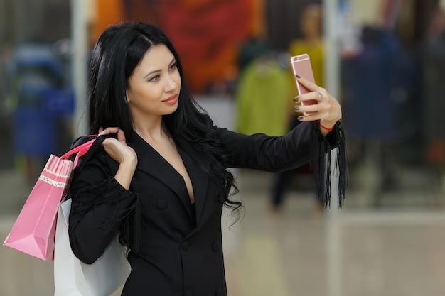 スマートフォンを使ってモールで自分撮り写真を撮る買い物袋を持ったセクシーな少女。