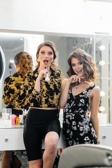 セクシーな若い女の子は楽しみを持ち、鏡の前でパーティーをします。ファッションと美しさ。