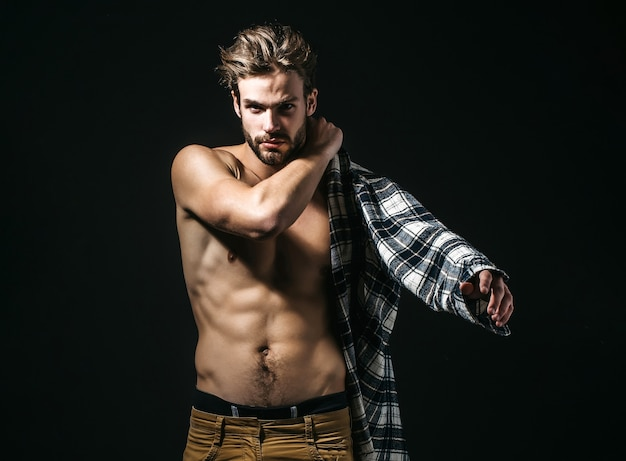섹시 한 젊은 잘 생긴 남자는 어둠에 격자 무늬 셔츠를 입으십시오