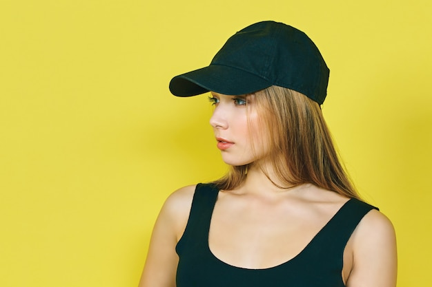 Sexy young hip hop woman in cap. on a yellow wall