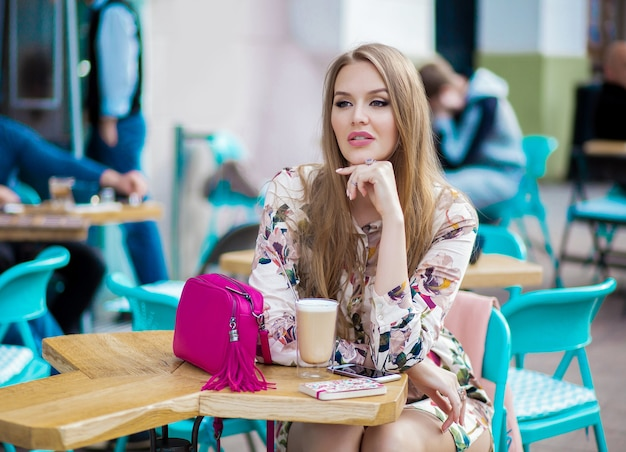 カフェに座っているセクシーな若い流行に敏感なスタイリッシュな女性、春夏のファッショントレンド、コーヒーを飲む