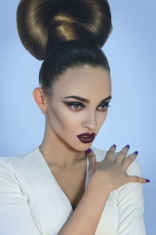 Sexy young lady with creative hairstyle and beautiful make up in studio
