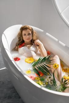 Сексуальная молодая стройная женщина принимает молочную ванну с цветами и тропическими листьями
