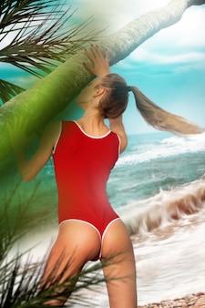 ビーチで赤いボディ水着とサングラスで美しい丸いお尻を持つセクシーな若いスリムな女の子