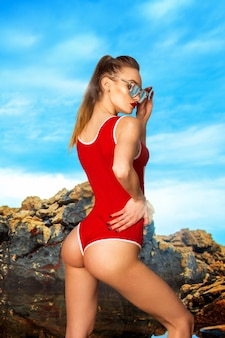 Sexy young slim girl with beautiful round buttocks in red body swimsuit and sunglasses on the beach