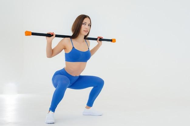 Сексуальная молодая спортсменка выполняет спортивные упражнения на белой стене