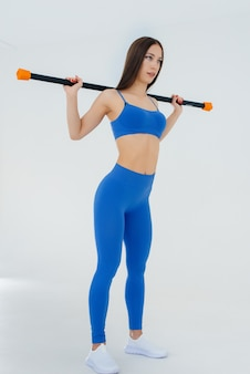 Sexy young sportswoman performs sports exercises on a white wall