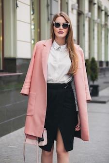 Giovane bella donna alla moda sexy che cammina in strada, indossa cappotto rosa, borsa, occhiali da sole, camicia bianca, gonna nera, vestito di moda, tendenza autunnale, sorridendo felice, accessori