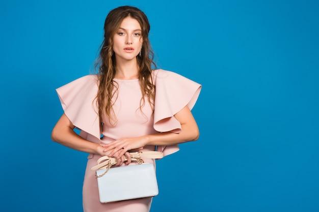 Giovane donna sexy elegante sexy in vestito di lusso rosa, tendenza moda estiva, stile chic, sfondo blu studio, che tiene borsa alla moda