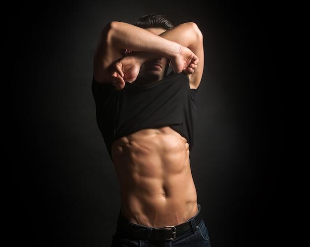 벌거 벗은 근육질의 몸통과 아름다운 몸매로 옷을 벗고 검은 셔츠에 섹시한 젊은 세련된 사려 깊은 남자