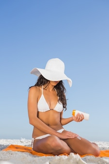 Sexy young woman applying sun cream while sitting on her towel